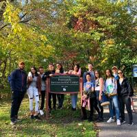 Group of people surrounding sign with text 'Pennypack Environmental Center'