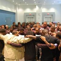 Group of african american men with their arms around each others shoulders in a circle